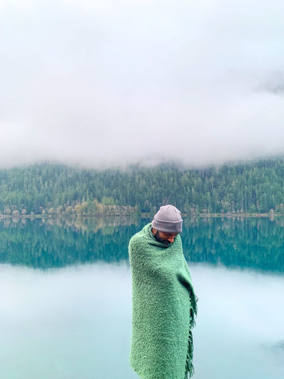 Man wrapped in blanket standing against lake during winter