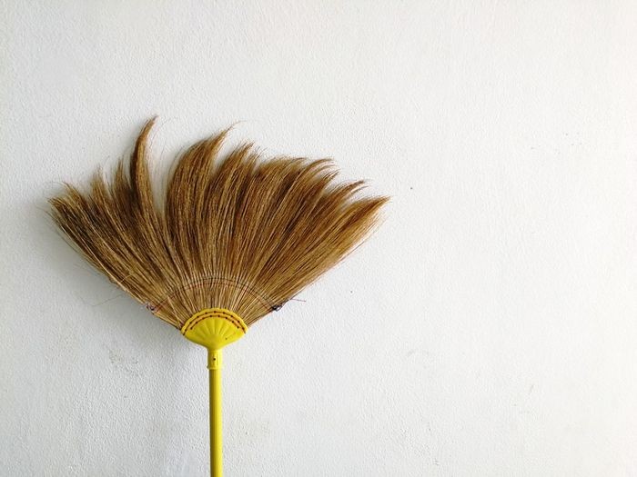 Close-up of broom against white wall