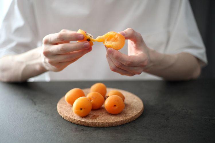 Close-up of man holding orange fruits