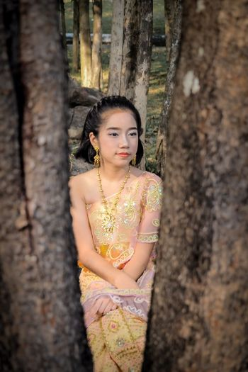 Girl in traditional clothing sitting at park