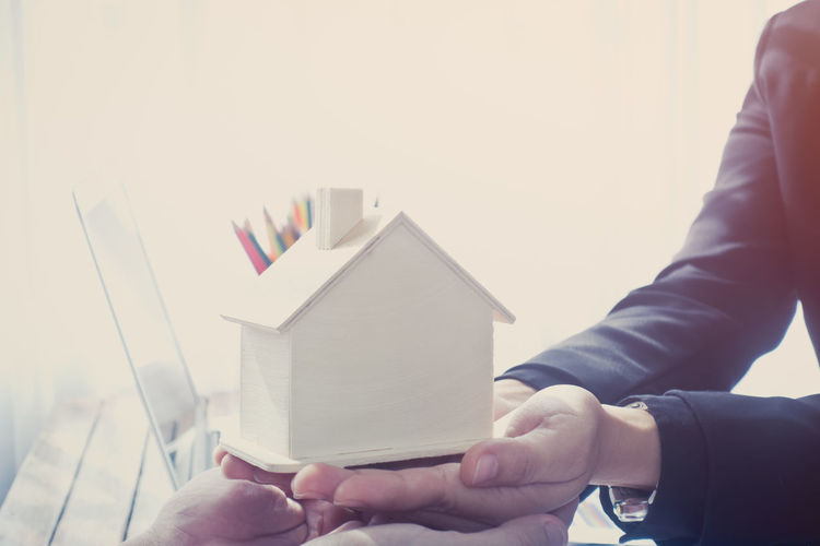 Close-up of salesman holding model home by laptop at table