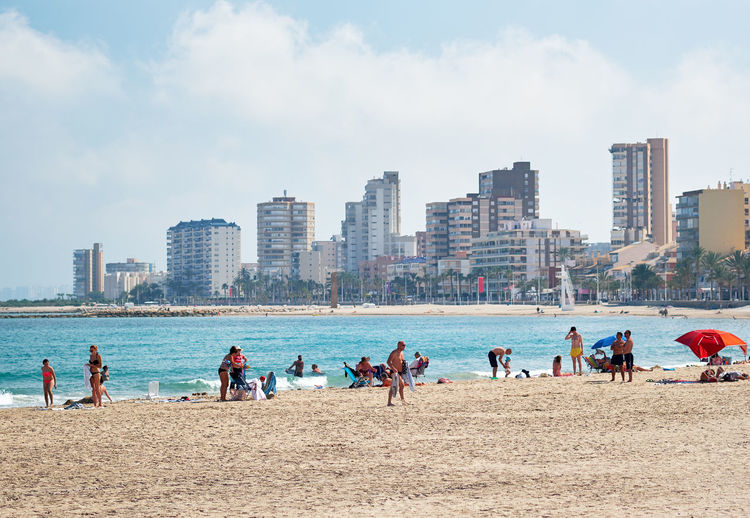 People At Beach In City Against Cloudy Sky