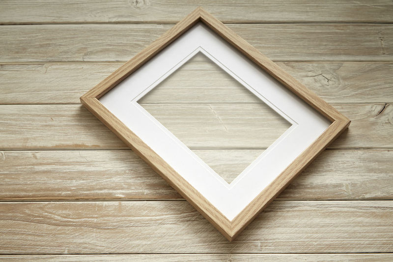 Close-up of blank picture frame on wooden table