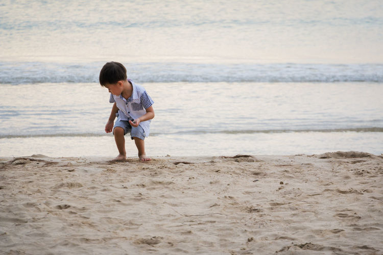 Boy playing on shore at beach