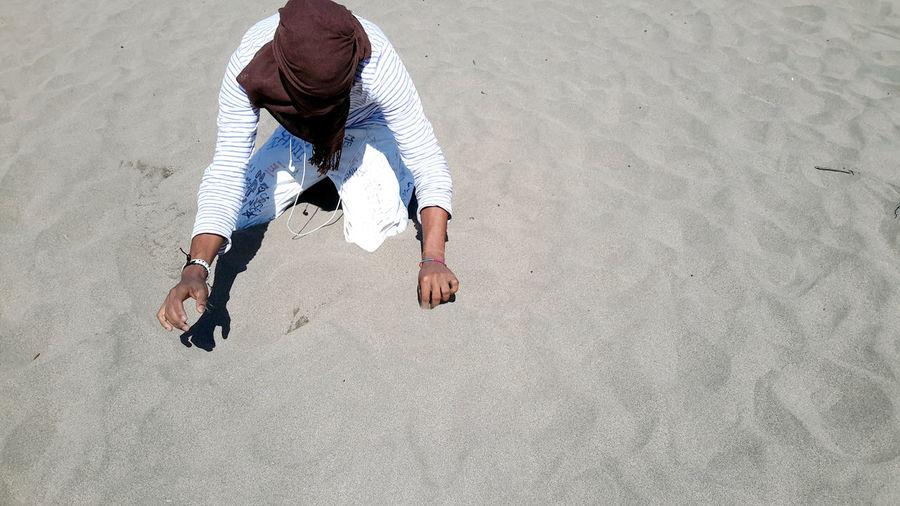 Unrecognizable person kneeling on sand