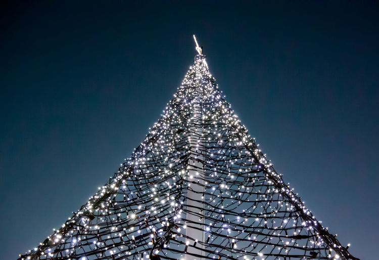 Low angle view of illuminated christmas tree against clear sky at night