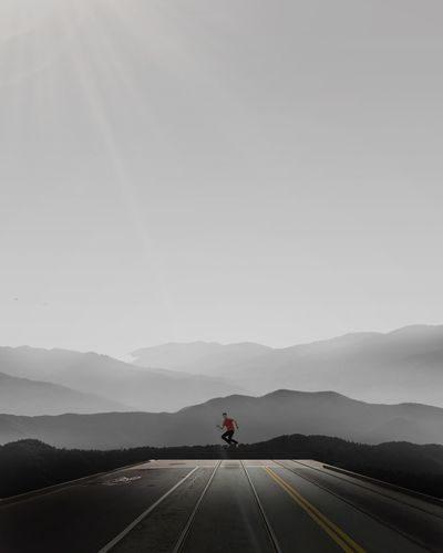 Distant view of man jumping over road amidst mountains against sky