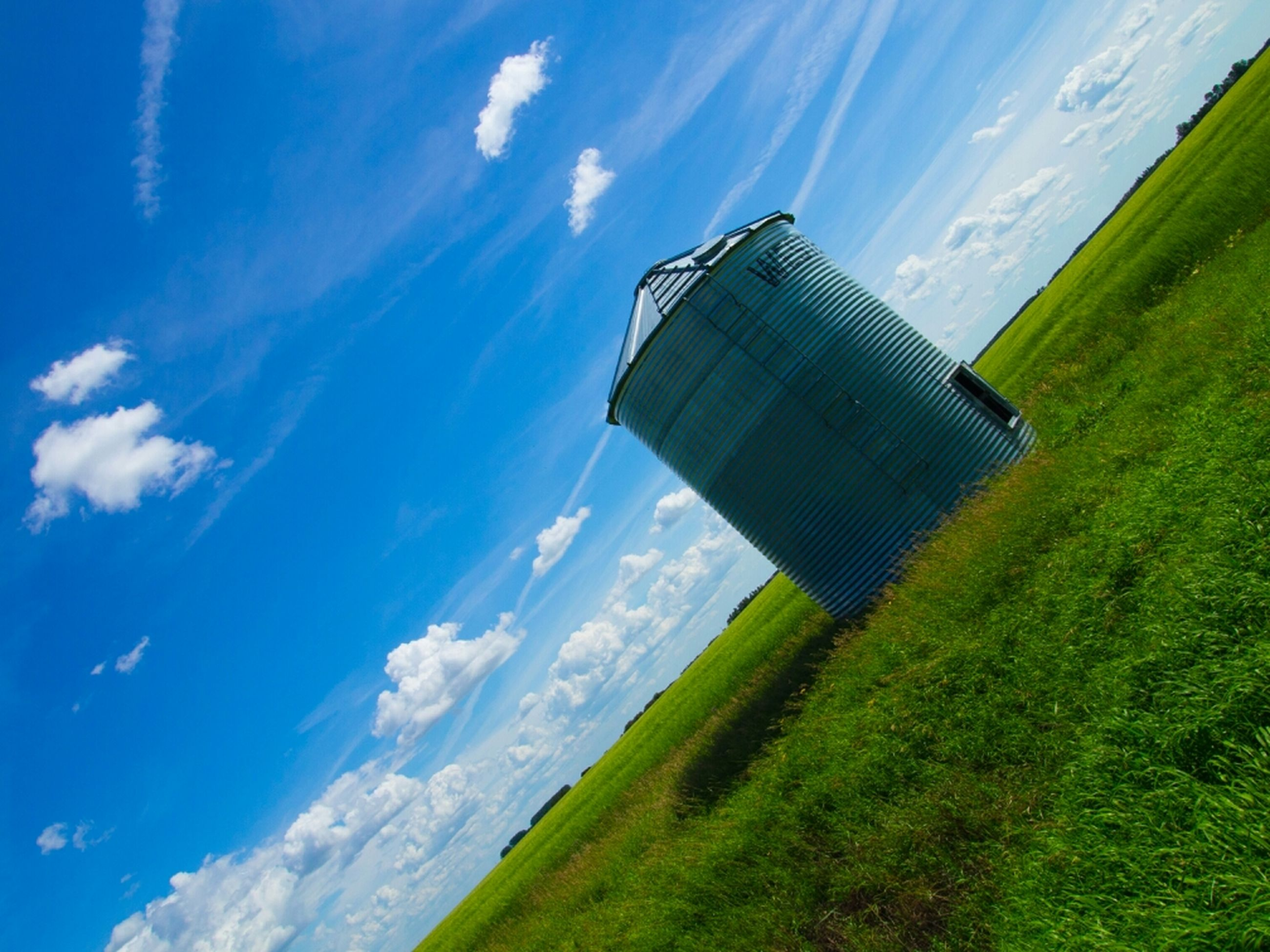 building exterior, architecture, sky, built structure, blue, grass, green color, landscape, cloud - sky, cloud, day, nature, field, sunlight, scenics, beauty in nature, outdoors, no people, tree, tranquil scene