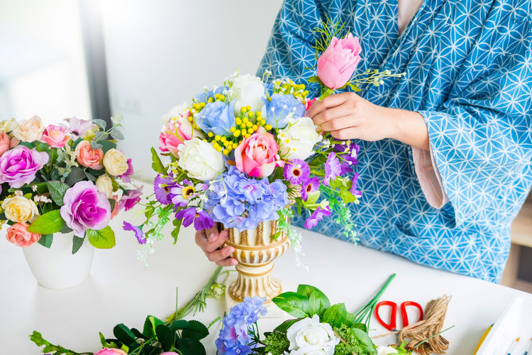 Midsection Of Woman Arranging Flowers