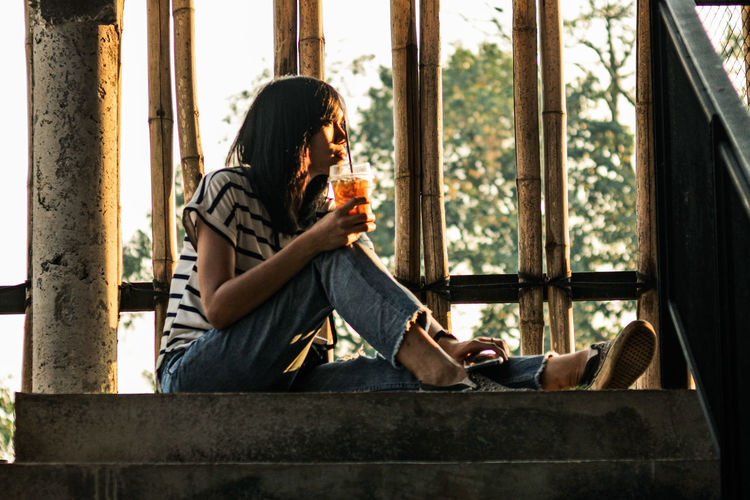 Thoughtful woman having drink while sitting on steps