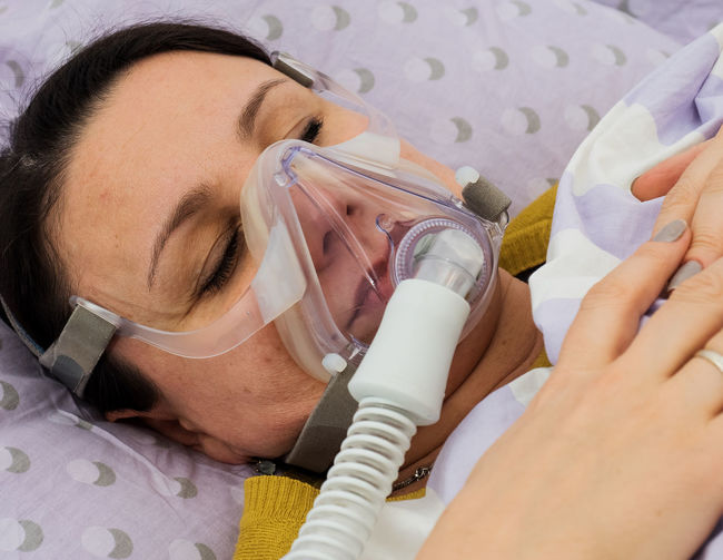 Close-up of female patient with oxygen mask sleeping on bed