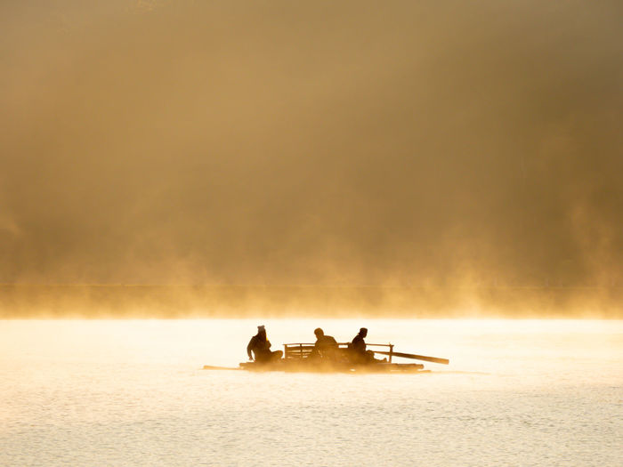 Silhouette picture of tourists ride on raft, there is a lot of fog floats in the natural reservoir.