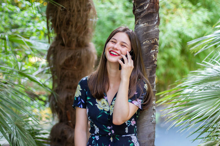 Smiling young woman using phone while standing against trees