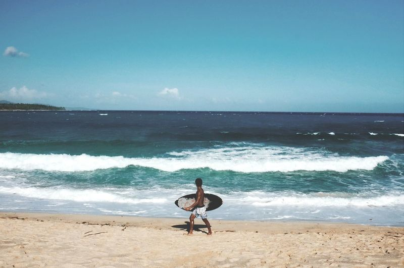 Man with surfboard walking on seashore at beach against sky