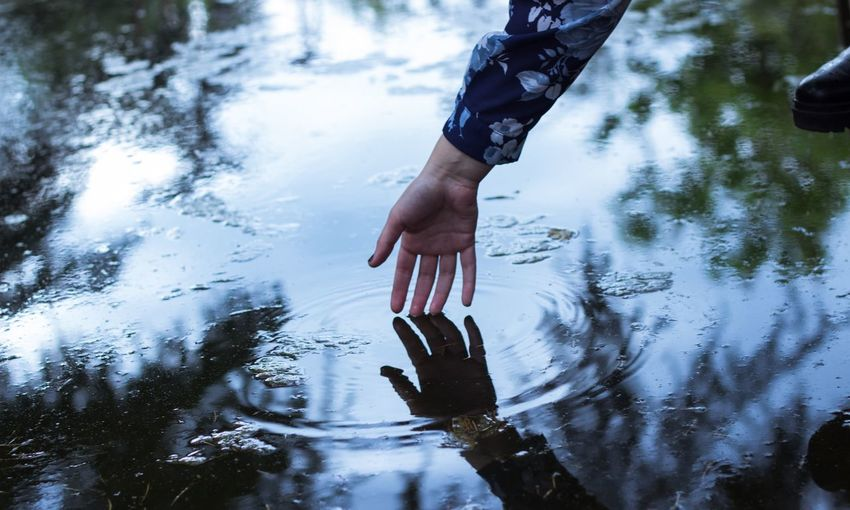 Cropped hand touching water