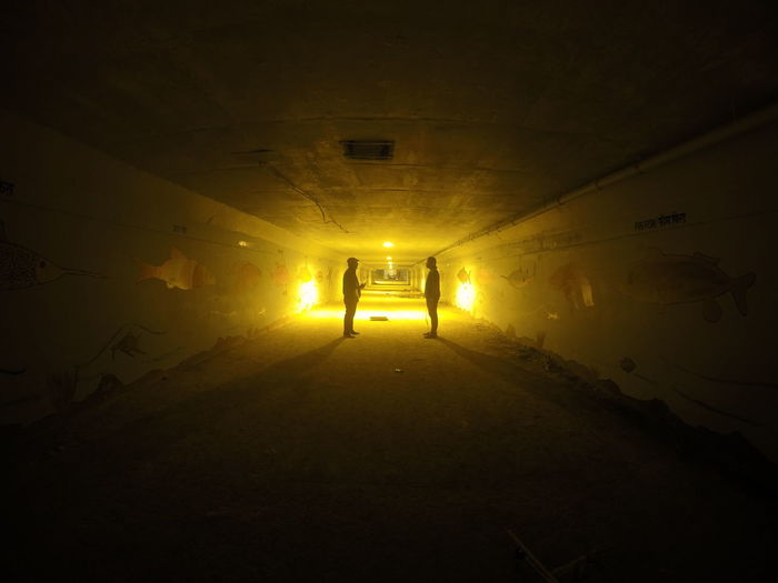 Side view of two silhouette people standing in tunnel