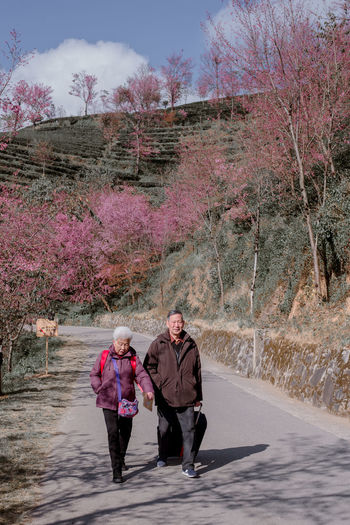 Rear view of people walking on road in winter