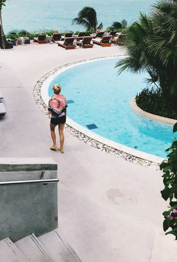 Rear view of woman walking by swimming pool