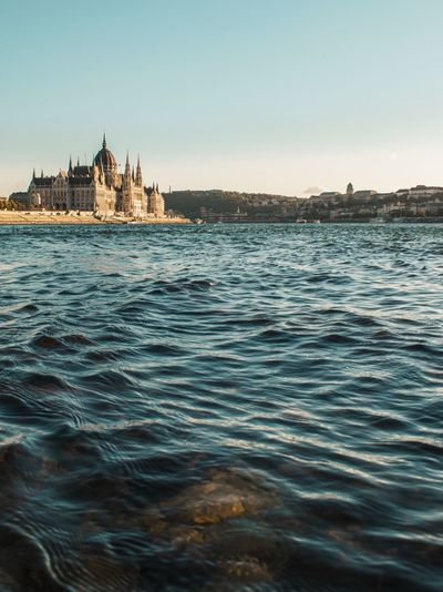 Hungarian parliament building by river against sky