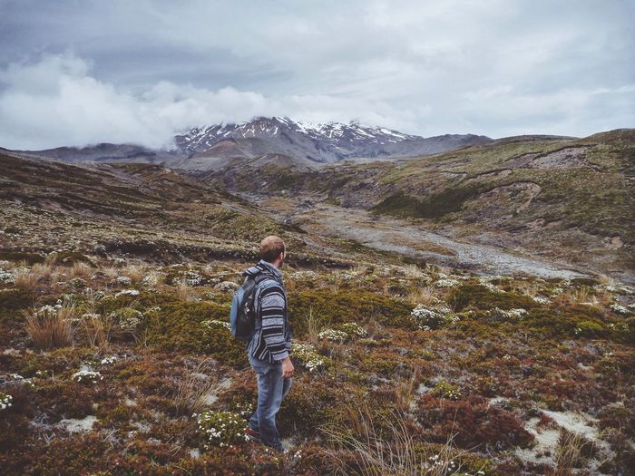 Side view of male hiker with backpack standing on mountain against cloudy sky