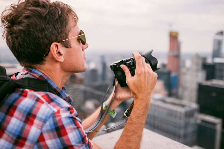 Portrait of young man photographing against sky in city
