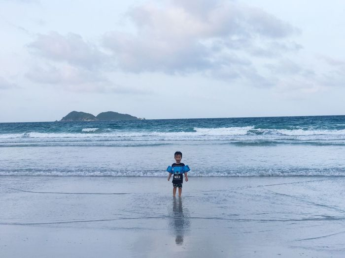 Boy Wearing Water Wings While Standing On Shore Against Sky