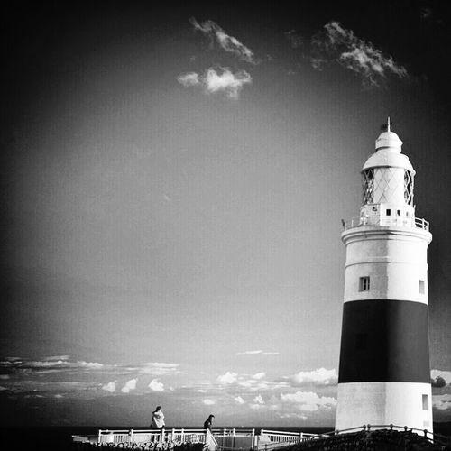 Lighthouse on sea against sky