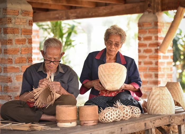 Senior couple making wicker baskets for sale