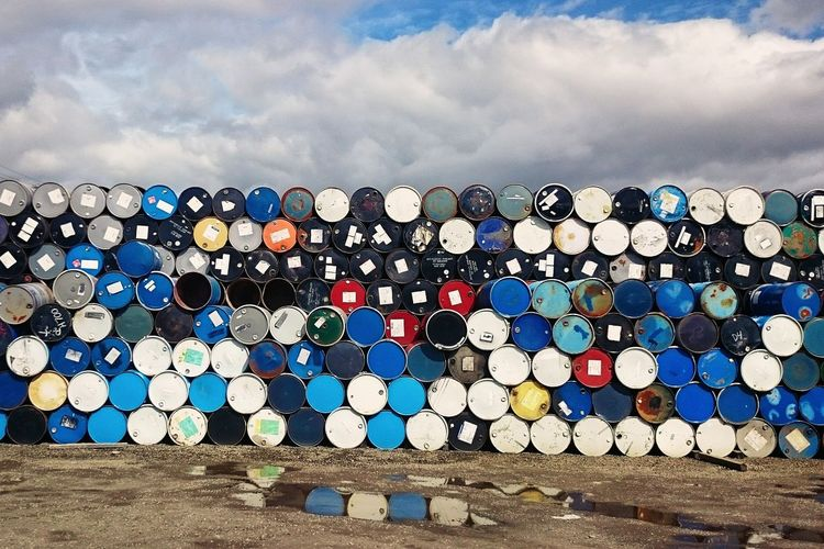 Stack Of Multi Colored Barrels Against Blue Sky
