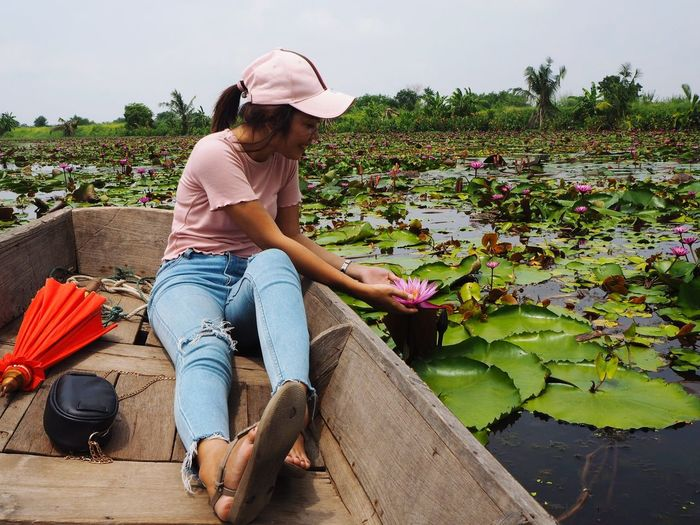 Full length of young woman touching lotus water lily while sitting in boat against sky