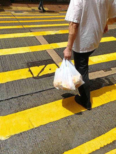 Low Section Of Man With Parcels Walking On Zebra Crossing