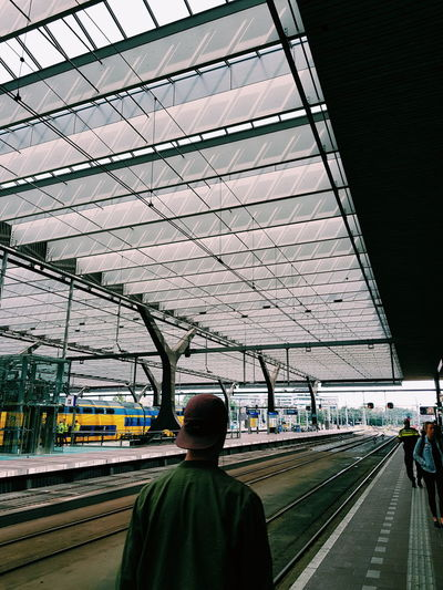 Rear view of man on railroad station against sky
