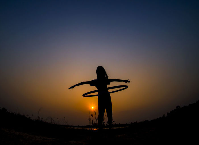 Silhouette girl playing with hula hoop crane against orange sky
