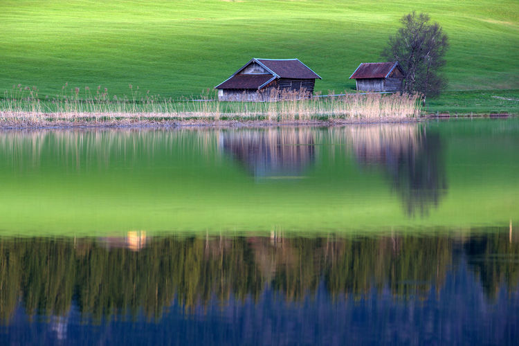 Scenic view of lake by house and building