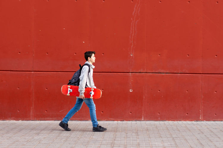 Full length of boy standing against red wall