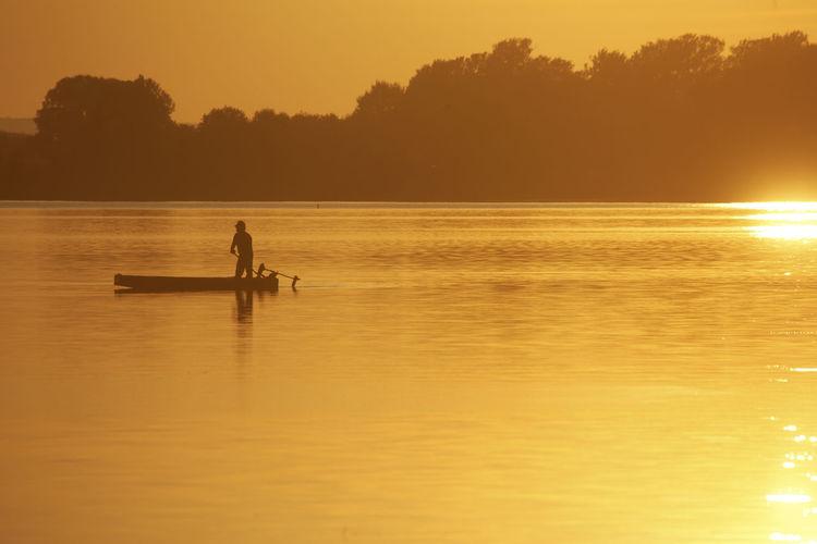 Silhouette people in boat on sea against orange sky