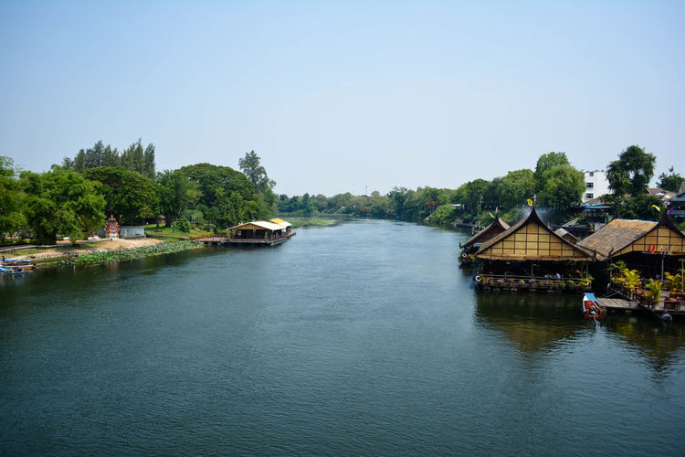 Scenic view of river by buildings against clear sky
