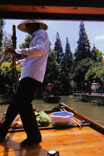 the strength of everyday life of a chinese ferryman Everyday Life People Water Town River Canon Beauty Ferryman Hat Strongman Strong China Zhujiajiao Strength Man Photographer Photo Photography Real People One Person Full Length Lifestyles This Is Strength EyeEmNewHere