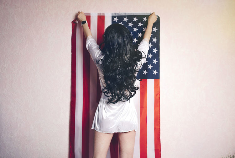 Girl with black hair in a negligee hangs an American flag on the wall of the house One Person Rear View Wall - Building Feature Standing Real People Casual Clothing Women Lifestyles Indoors  Hair Long Hair Holding Hairstyle Three Quarter Length Young Women Adult Day Arms Raised Flag USA America Legs Patriotism My Best Photo International Women's Day 2019