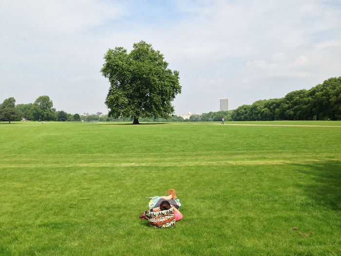 One person laying on green field