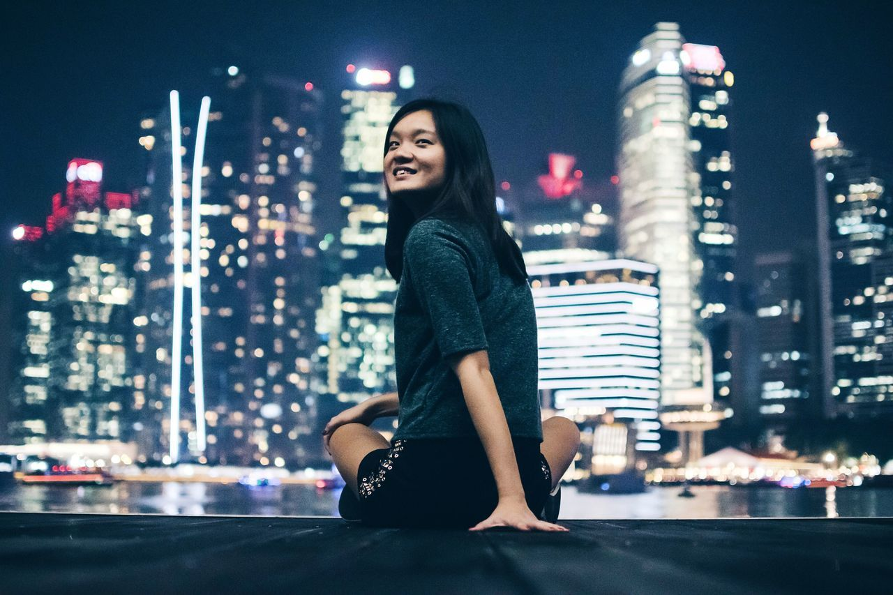 Rear view of happy young woman against illuminated cityscape