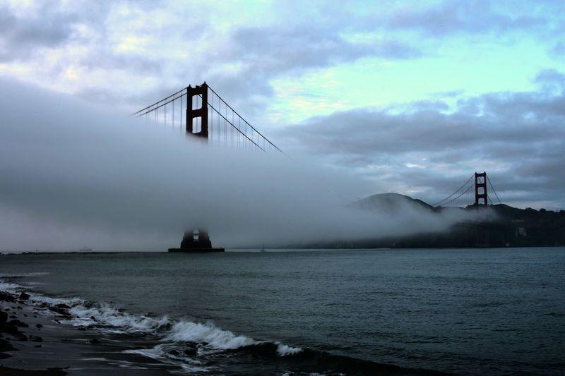 Golden gate bridge covered in fog over bay against sky