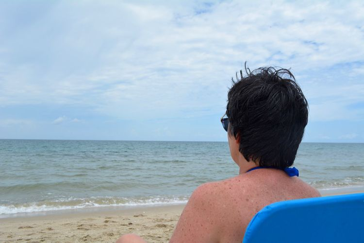 Rear view of mature woman looking at sea while sitting on deck chair against sky