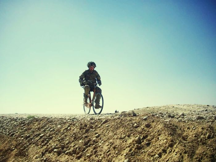 Soldier riding a bicycle in afghanistan One Person One Man Only Only Men Full Length Adults Only Danger Cycling People Adult Outdoors Clear Sky Sky Bicycle Headwear Adventure Day Sport Mountain Bike Men Cycling Helmet EyeEm Best Shots EyeEmNewHere Eye4photography  War