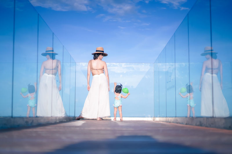Rear view of woman standing with daughter against sky