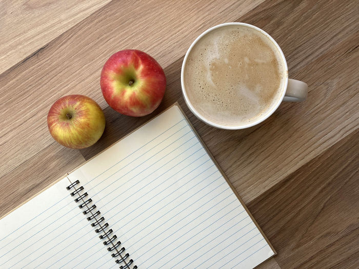 High angle view of apples and coffee on table