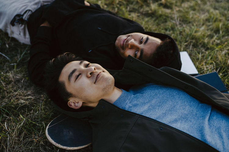 Rear view of couple lying on land