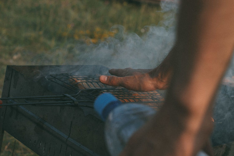 Cropped hands of man over barbecue grill