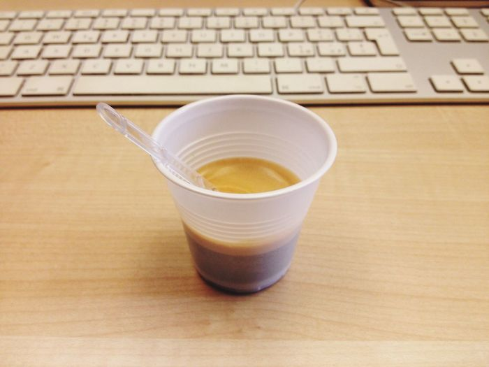 Coffee close to keyboard on home office desk table