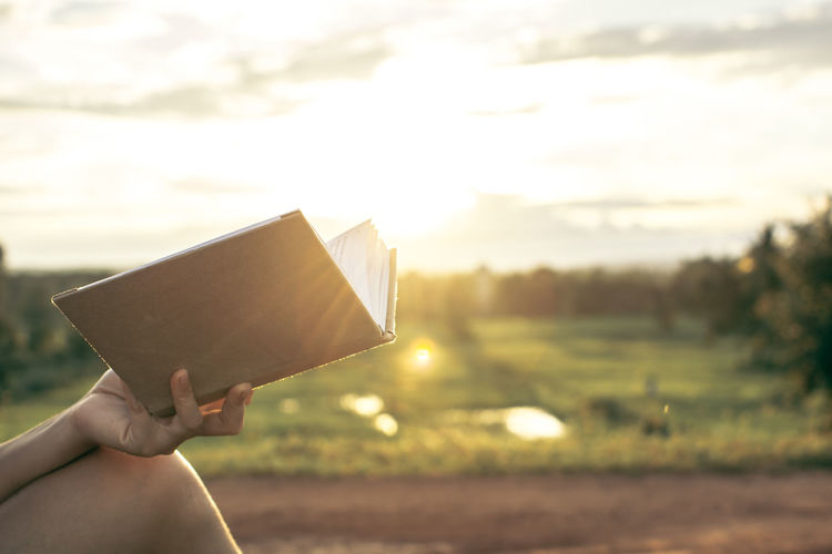 Midsection of person holding book against sky during sunny day